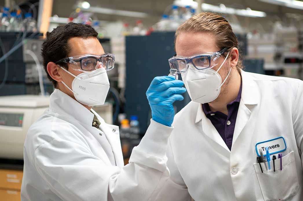 two scientists with masks and glasses looking a vial